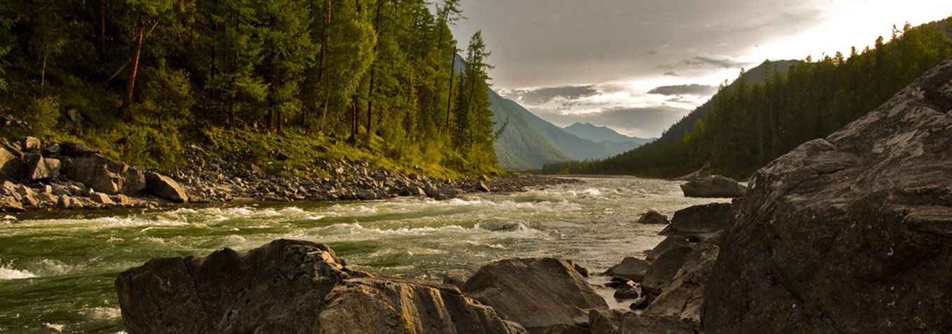 Image is of mountains with a river, trees are lining the riverside