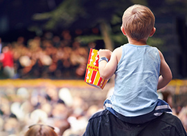 Child sitting on adults shoulders holding a bag of popcorn