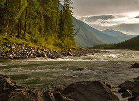 Image is of mountains and a river, with trees lining the river side