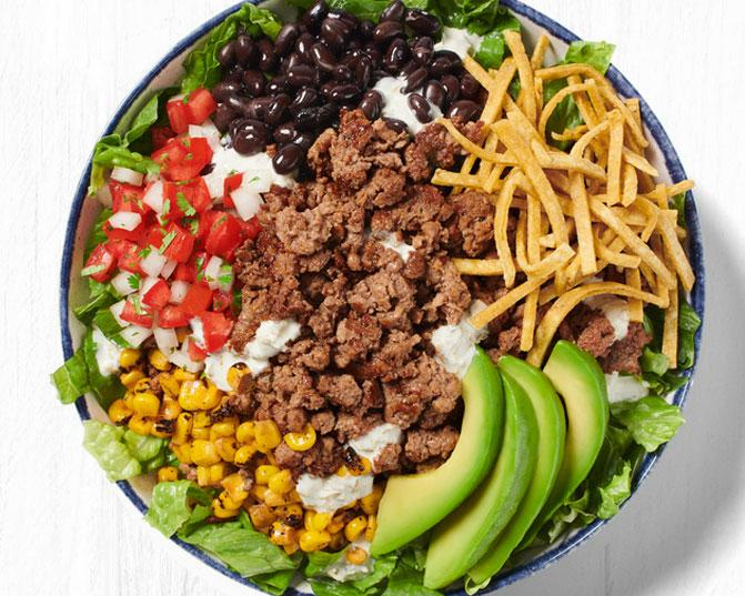 Avocado Corn Taco Salad with crisp romaine, black beans, roasted corn, salsa fresca, tortilla strips, sliced Hass avocado and signature pickled jalapeno ranch dressing.